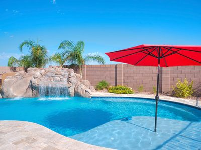 Large outdoor pool with surrounding locking safety gate, grotto, and waterslide!