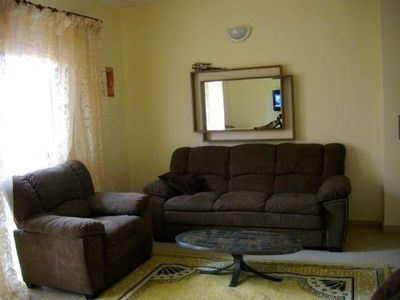 1 living room with 2 sofas, 2 armchairs, 1 table, 1 flat screen TV (with satellite channel) with large bay window openin