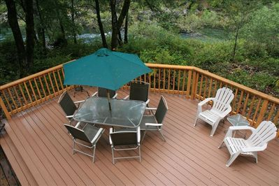 """A portion of our deck showing proximity to the river, a """"stones throw""""."""