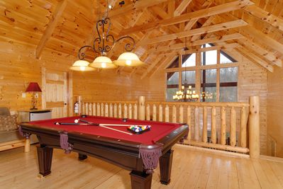 Cathedral ceilings with exposed beams, slate top pool table in the game loft