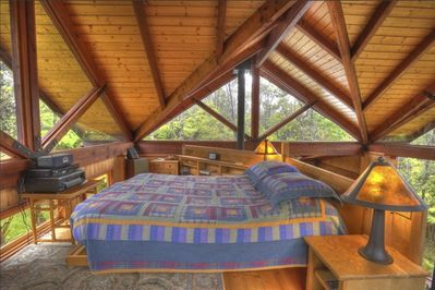 The sleeping loft is surrounded by windows.