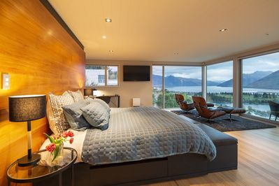 Spacious master bedroom with Smart TV, desk and multiple lounge options