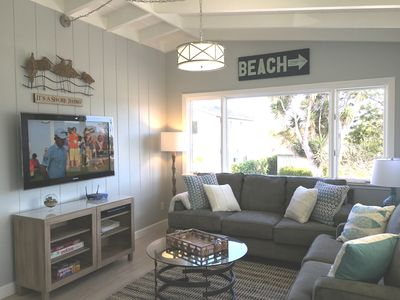 Bright, sunny living room with large windows to let in the ocean breeze
