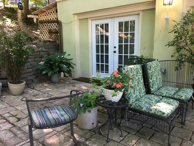 Outside entrance with seating and flowers on patio