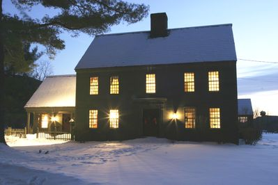 Front of the house in winter twilight. Warm and cozy inside.
