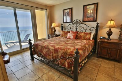 Master bedroom with a king size bed and access to the balcony.