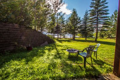 features a backyard with plenty of green and mature trees.