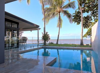 Sparkling salt pool with sea views surrounded by glass pool fence.