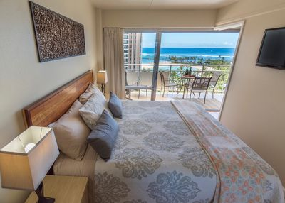 King size bed with TV on the wall and ocean views
