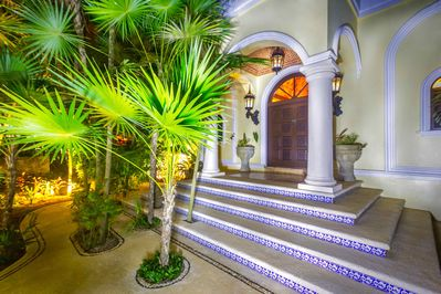 Our lush tropical gardens lead you to our main entrance with hand carved door,