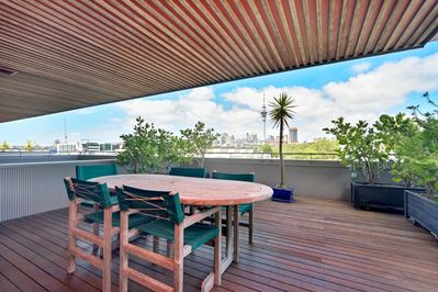 Large rooftop deck with views of Victoria Park and the city skyline