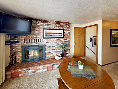 """Living Room - Cozy up next to the brick-lined fireplace and watch shows on a 32"""" TV with cable."""