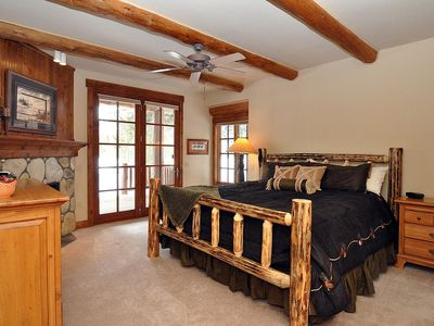 Main floor master bedroom with king bed, fireplace and walk-out deck