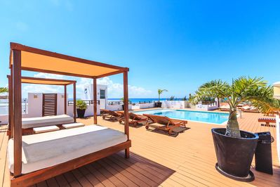 The Casa del Mar rooftop pool area with ocean view, beds, lounge chairs