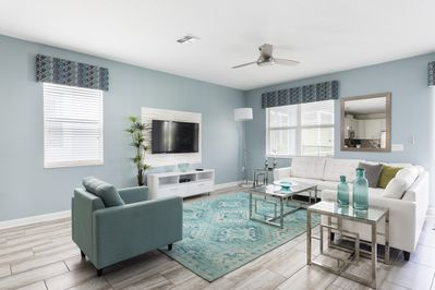 decorated living room with flat TV, ceiling fan and coffee table of championsGate resort villa