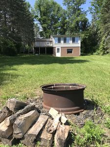 Fire pit and back of cottage with views of the large, private space outdoors!