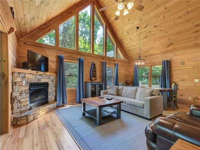 Country comforts - The cozy sofas, the stone-surround fireplace, and the wood-planked walls and cathedral ceiling add to the living room's rustic charm.