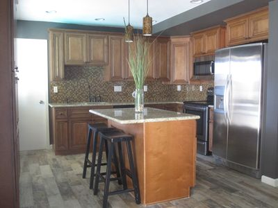 Granite and stainless steel kitchen with breakfast bar and cookware