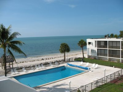 Bird's eye view of pool & beach from roof of building. See our balcony top right