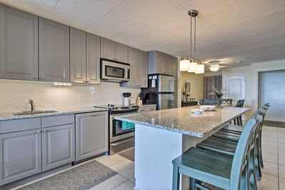 The unit features a fully equipped kitchen with granite countertops.