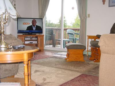 Living room with new laminate flooring and large area rug.  Patio door to deck.