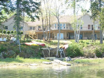 back of home, horseshoe pit , firepit, dock and hot tub