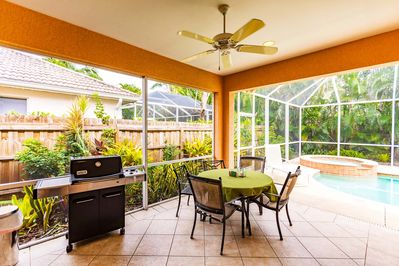 Lanai seating by the pool with gas grill