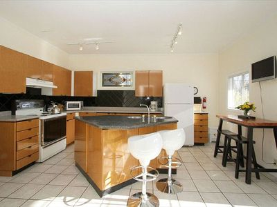 Large entertaining Kitchen with island, wall mounted flat screen TV