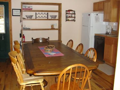 Kitchen has ample seating and storage shelves and cabinets.