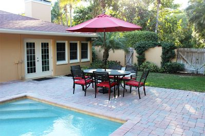 Private pool deck and backyard with lush tropical plantings.