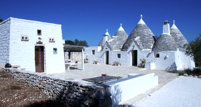 Photo for Magnificent trullo Cisternino immersed in Mediterranean scrub -