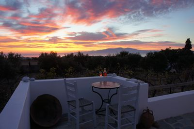Chilled house rosé at sunset, looking over our olive grove, sea & Paros
