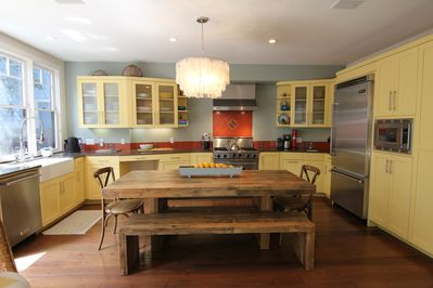 Roomy chef's kitchen with a large farm table, anchors meals, meetings and work.