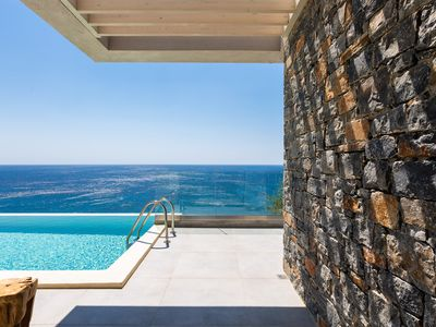 Photo for Walking distance to the beach, dazzling sea view & heated infinity pool!