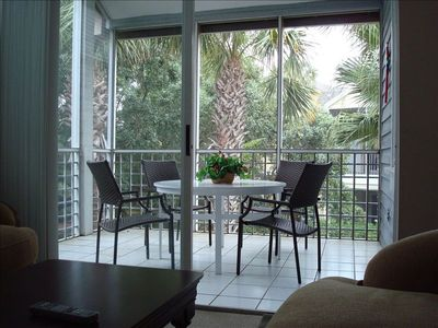 """Private """"tropical treehouse"""" screened in porch off the living room."""