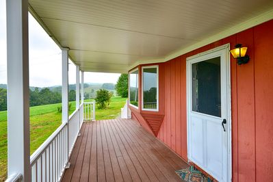 The front porch boasts views of the 48-acre property & rolling New York hills.