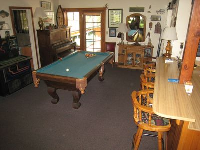 Game area off living room with jukebox, pool table, wet bar
