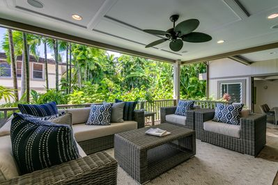 Covered lanai off of living room, with outdoor kitchen off in the distance