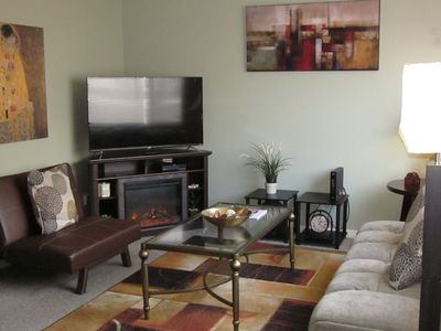 """Living room with warm electric fireplace and 50"""" Smart TV."""
