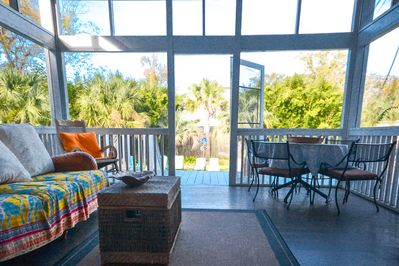 Screened porch overlooks pool and yard. TV, Table, rockers, couch. ceiling fan