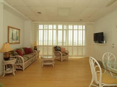 Spacious living room View of boardwalk & beach through plantation shutters