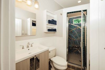 The full bathroom has a single vanity, toilet and a double headed shower.