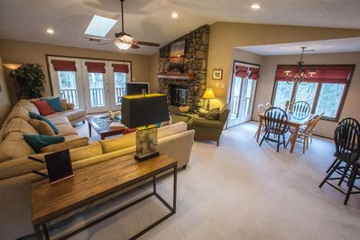 Spacious living area with lots of light. A stone fireplace too!
