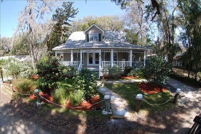 The Captains Cottage framed by old live oaks and a timely dirt road.