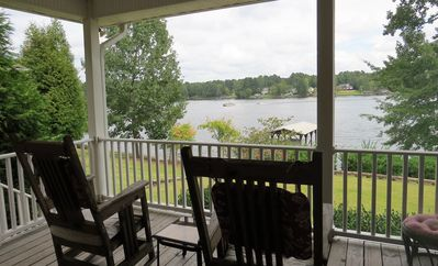 covered deck with rocking chairs and views of the lake
