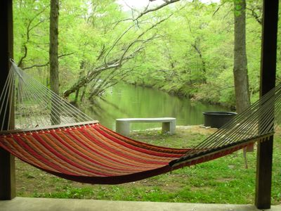 view from under the deck toward the creek with hammock, bench and firepit