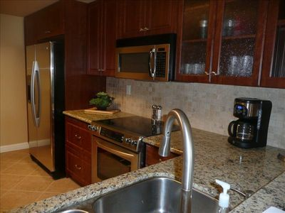 Kitchen with all new stainless appliances and granite counter tops with bar.