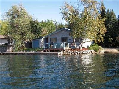 Photo of house from offshore with sandy beach on right and 40' long dock.