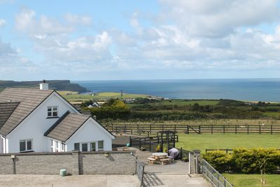 House showing decked patio/BBQ area, large secure fron garden with sea views.