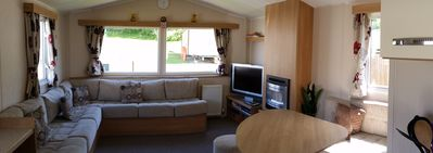 An open plan living area including the dining area with gas fire and sofa bed.